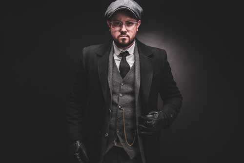 Peaky Blinders clothing Tommy Shelby look with a grey 3 piece suit, hat and black overcoat
