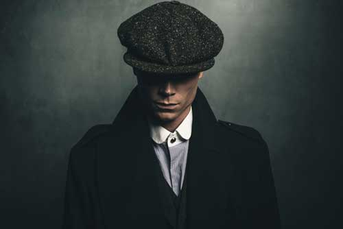 Peaky Blinders clothing style man with a hat, grey 3 piece suit and black overcoat