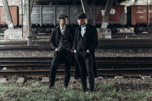 Peaky Blinders clothing two stylish gangsters men with black suits, waistcoats, ovecoats, and hats