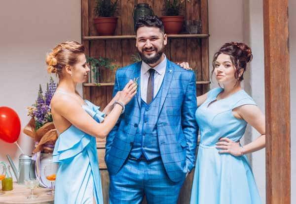 Groom in 3 piece wedding suit with bridesmaids on wedding day, indoors Happy Gentleman