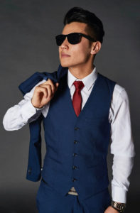 Men dressed with a blue waistcoat for men and white forlam shirt and red tie and sun glasses