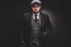 Men dressed with a Peaky Bllinders cap, hat, overcoat and three piece peaky blinders suit