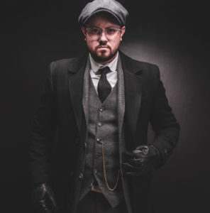 Peaky Blinders Suit. Man dressed as Tommy Shelby with a grey hat, three piece suit, overcoat, vintage watch and gloves.