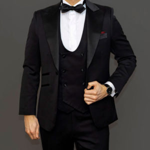 Man dressed in men's tuxedo suit. white shirt, black bowtie and watch
